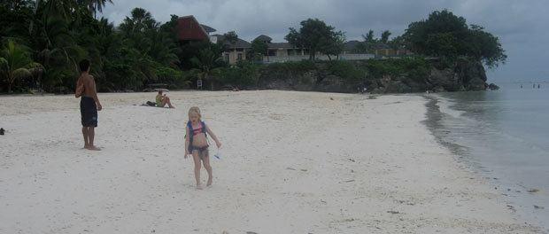 rejse til filippinerne med børn som packbacker - her går vores ældste med en rygsæk hen over stranden på panglao island