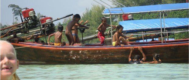på vores rejser generelt er børnene gode til at lege med lokaler - her ses de i vandet i thailand på koh lipe