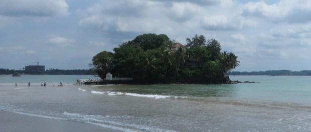 skøn strand med historisk ø ved weligama